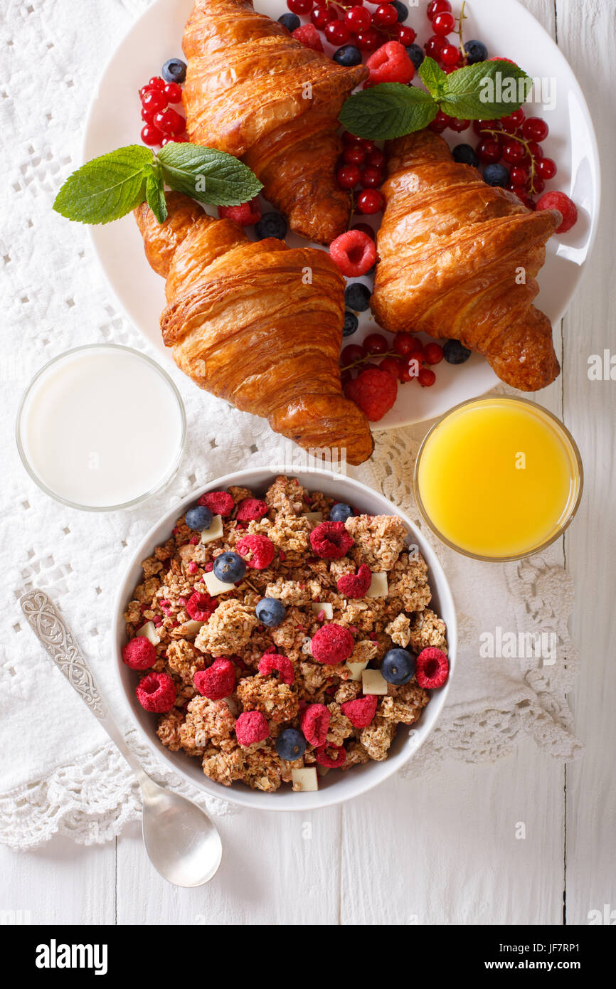 Muesli with berries and croissants, milk and orange juice close-up on the table. vertical view from above - Stock Image