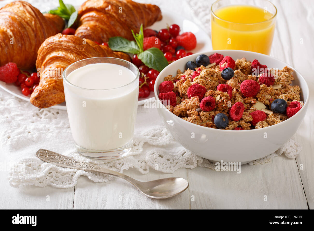 Homemade granola with berries, croissants, milk and juice closeup on the table. horizontal Stock Photo