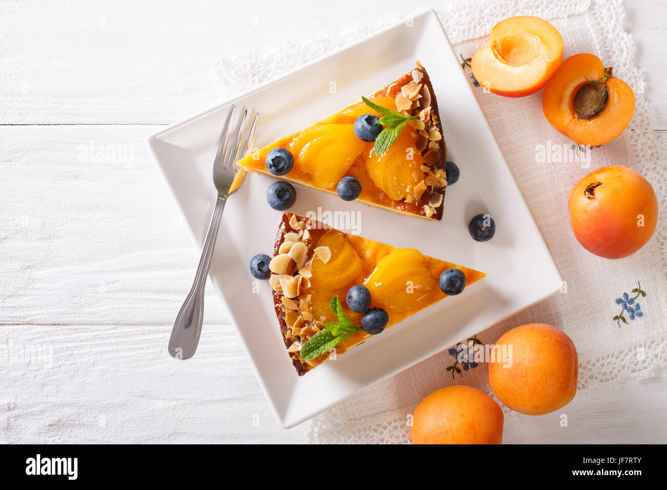 Apricot cheesecake with blueberry close-up on a plate. horizontal view from above - Stock Image