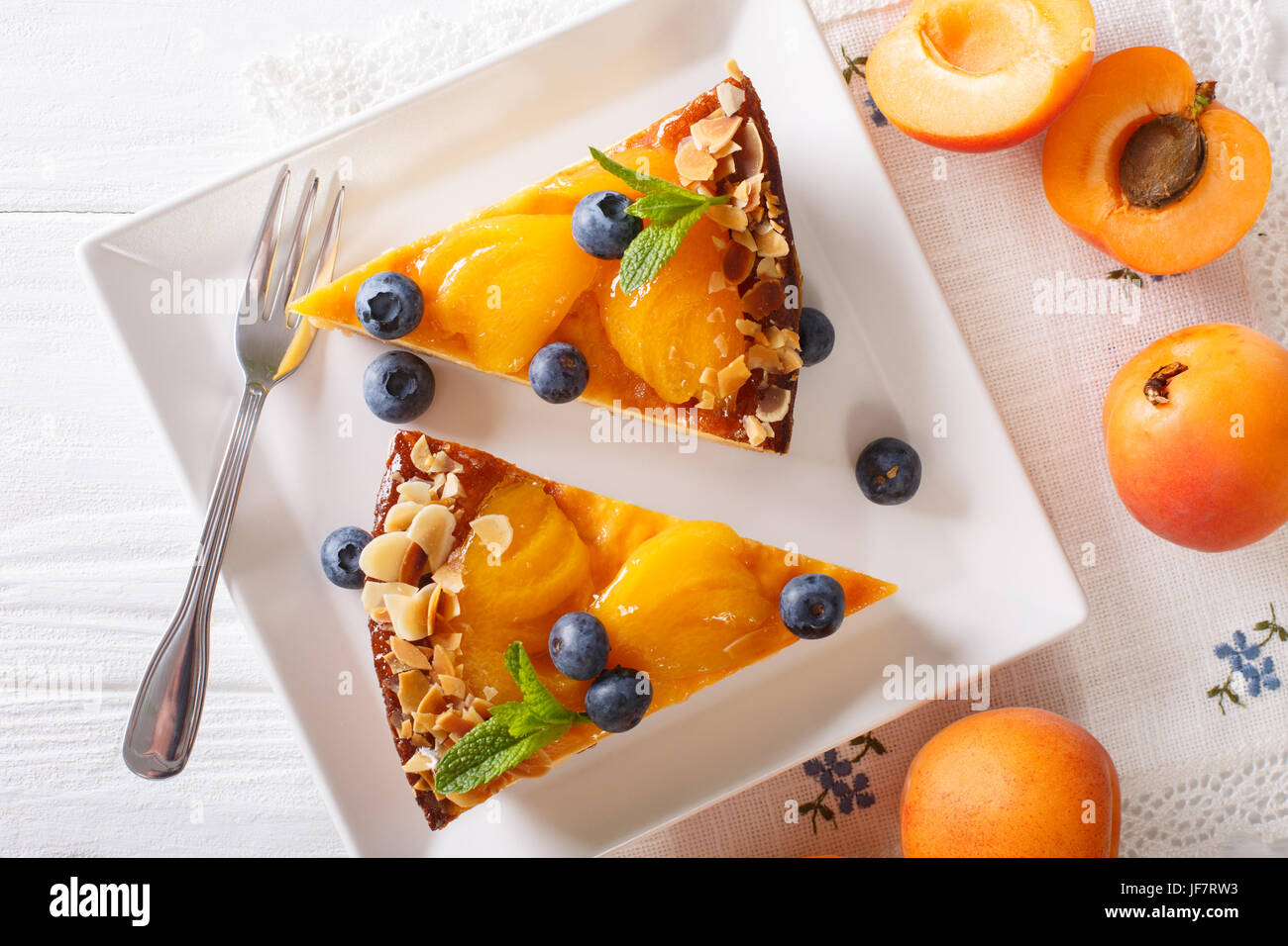 Apricot pie with blueberries and nuts close-up on a plate. horizontal view from above - Stock Image