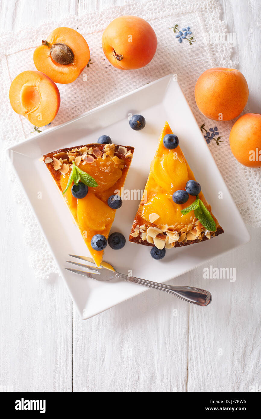 Apricot cheesecake with blueberry close-up on a plate. vertical view from above - Stock Image