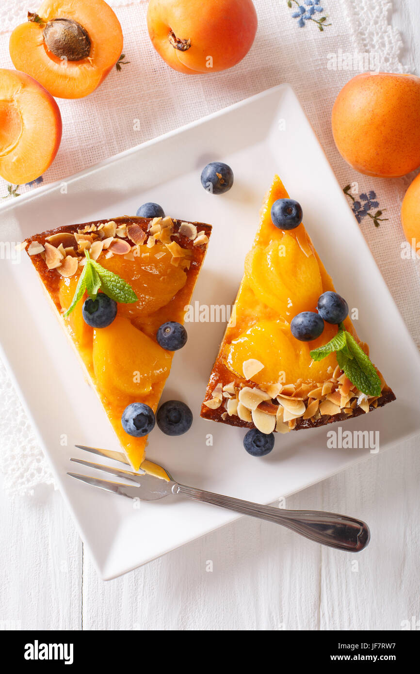 Apricot pie with blueberries and nuts close-up on a plate. vertical view from above - Stock Image