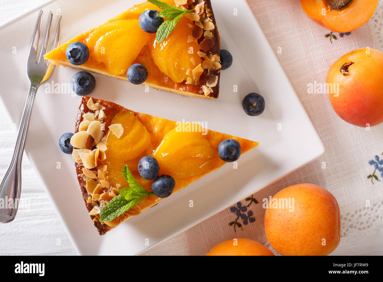 Apricot cake with blueberries, mint and nuts close-up on a plate. horizontal view from above - Stock Image