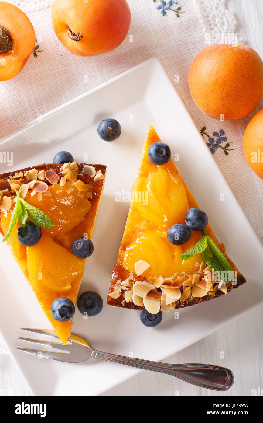 Apricot cake with blueberries, mint and nuts close-up on a plate. vertical view from above - Stock Image
