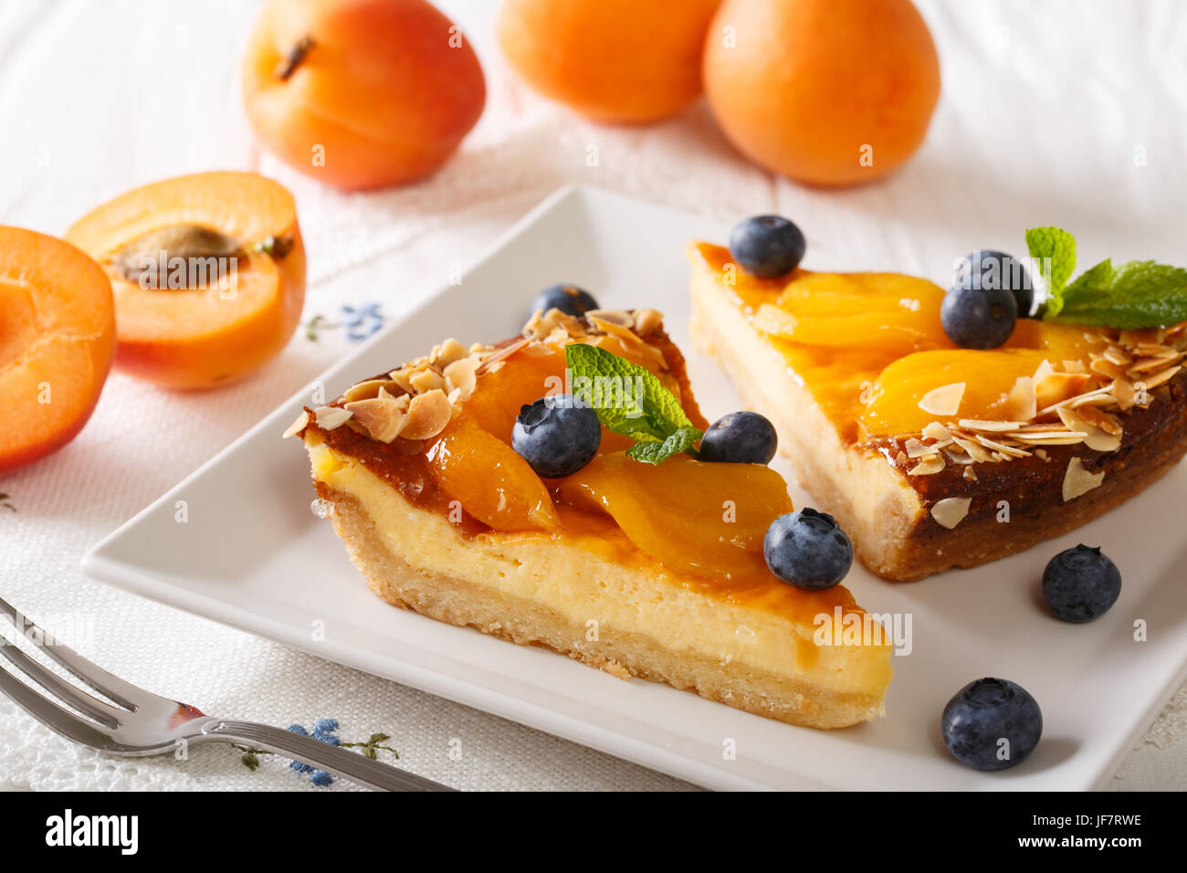 Beautiful apricot cheesecake with blueberries, mint and nuts close-up on a plate. horizontal - Stock Image