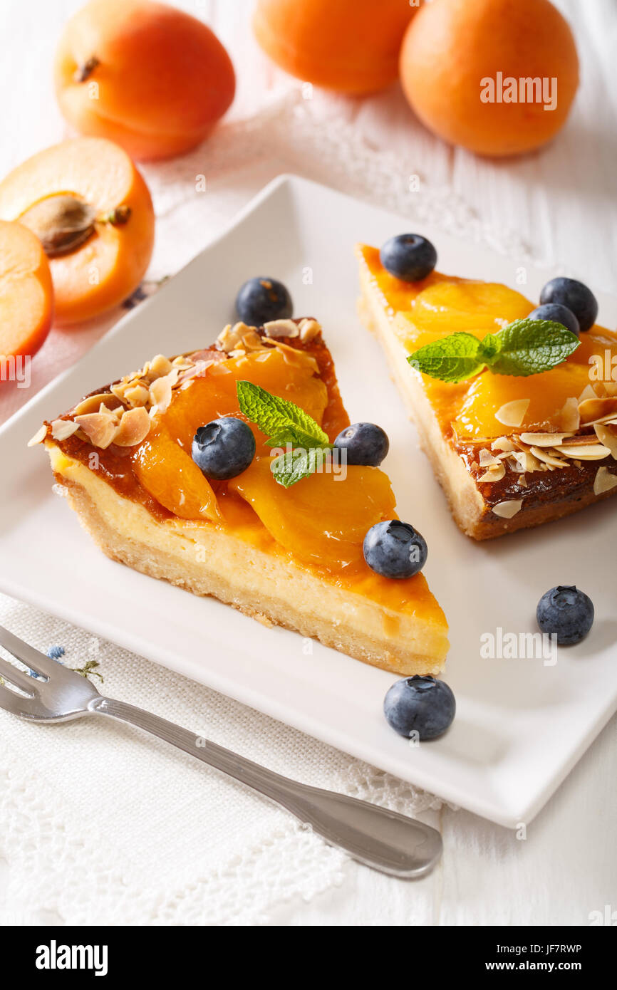 Apricot pie with blueberries and nuts close-up on a plate. vertical - Stock Image