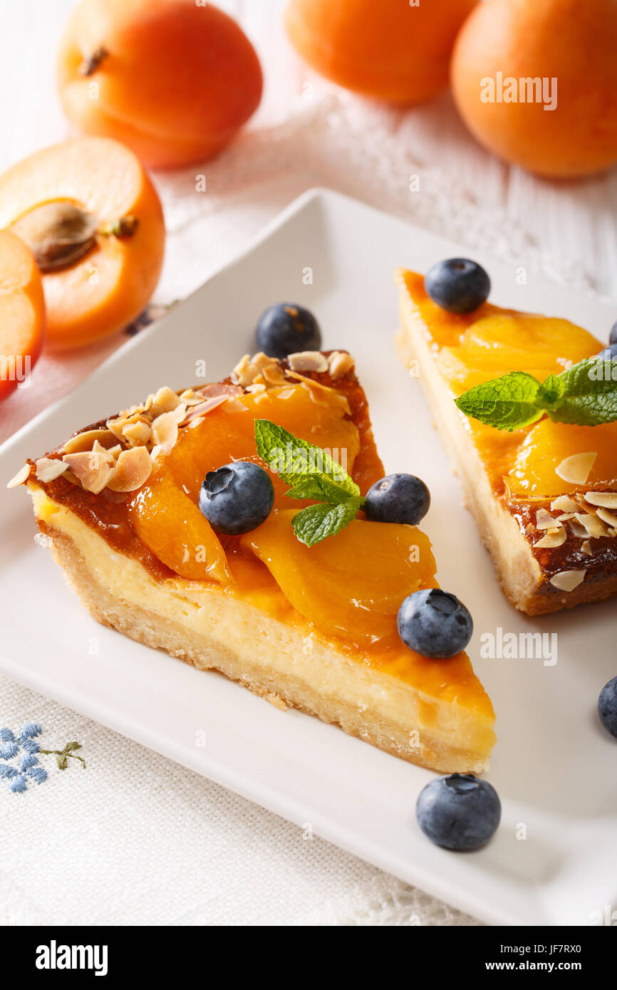 Cheesecake with apricots, blueberries, mint and almonds close-up on a plate on a table. vertical - Stock Image