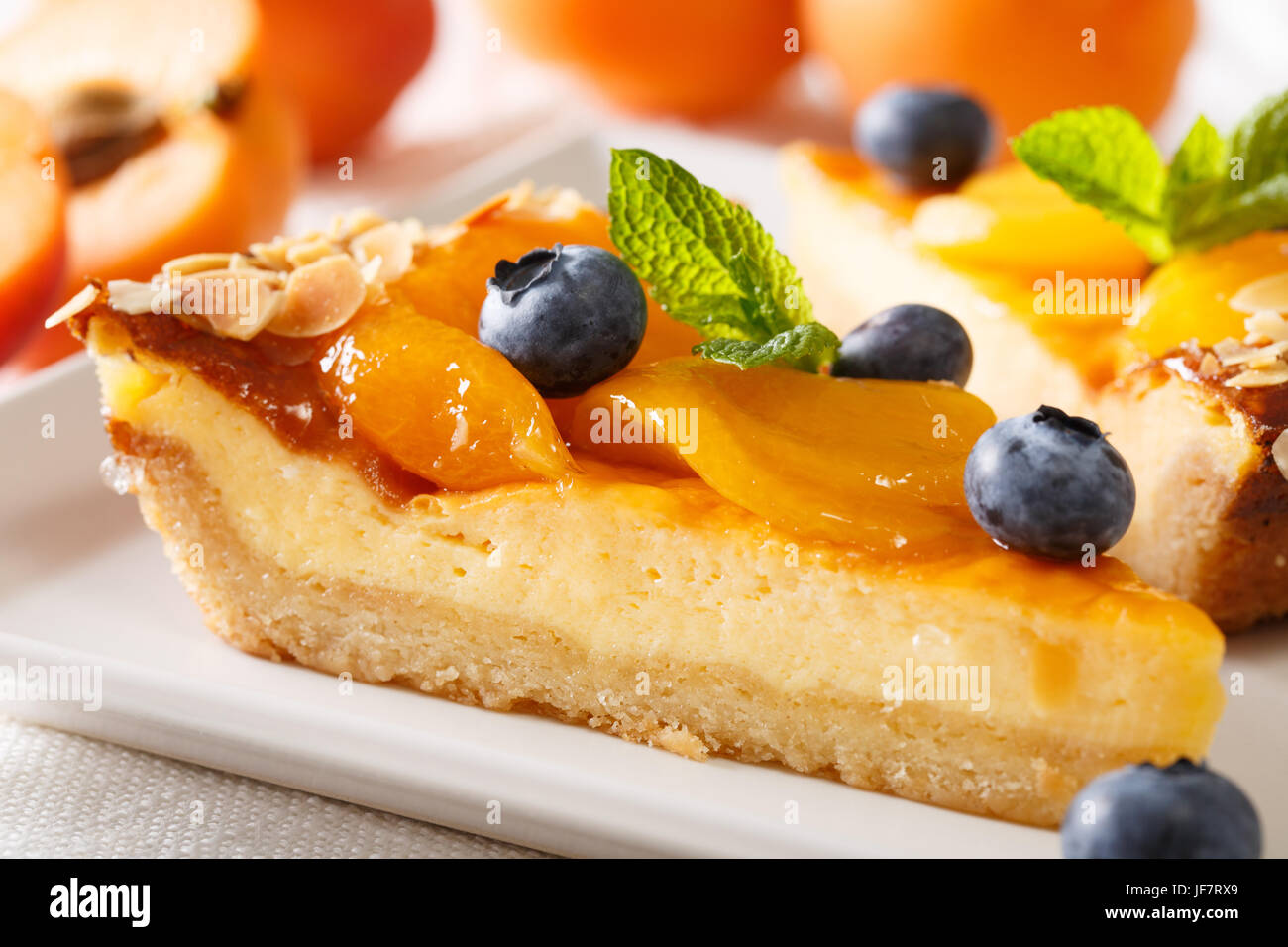 A beautiful dessert: a cheesecake with apricots, blueberries and almonds close-up on a plate. horizontal - Stock Image
