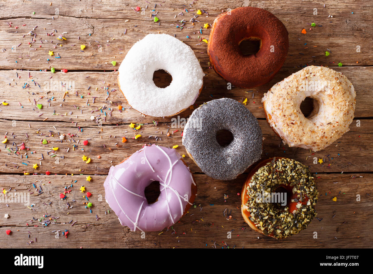 Multicolored donuts with fillings close-up on the table. horizontal view from above - Stock Image