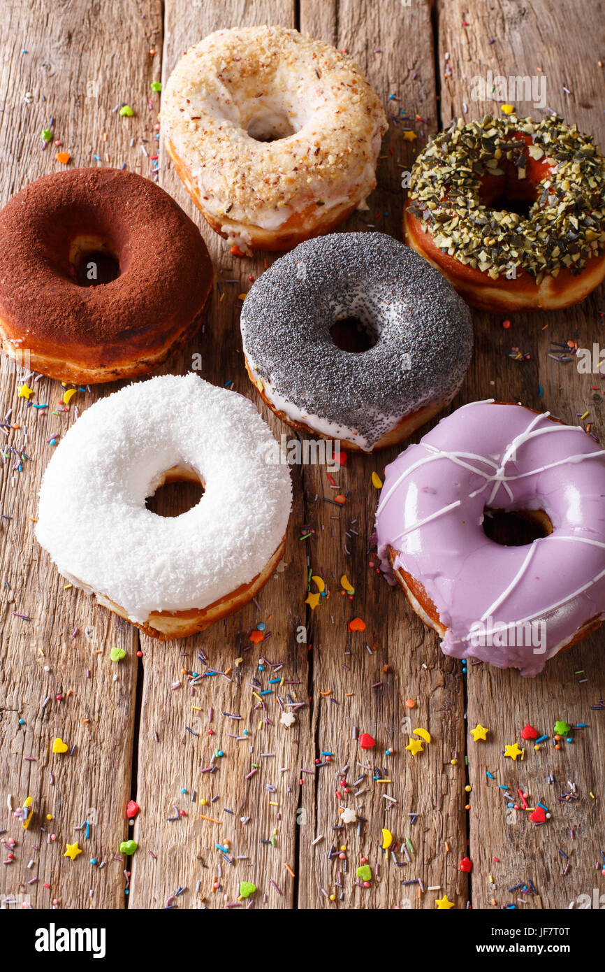Tasty multicolored donuts with fillings close-up on the table. Vertical - Stock Image
