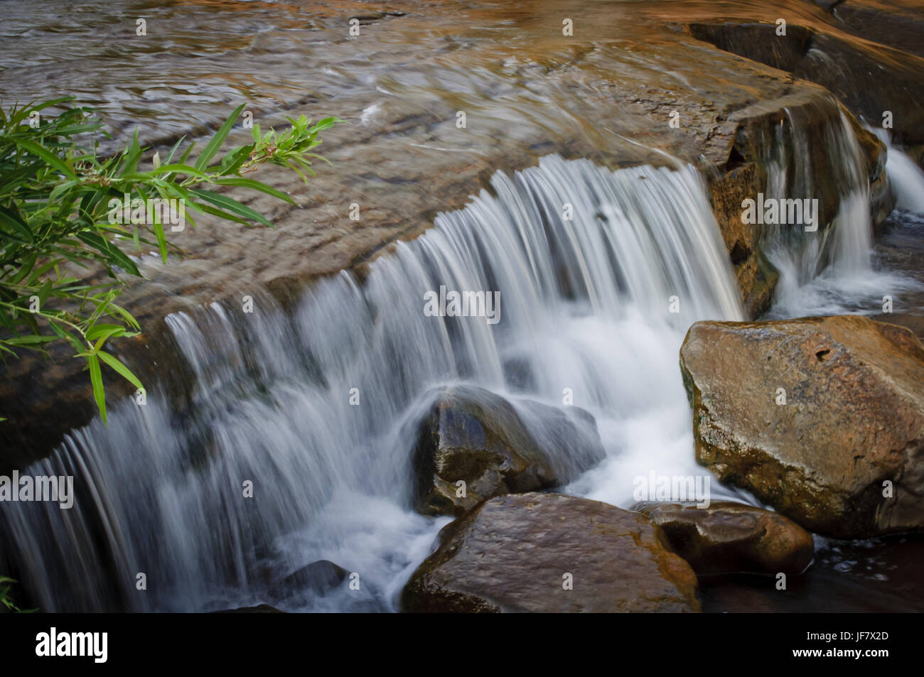 Fresh water flowing over rocks on a creek. - Stock Image
