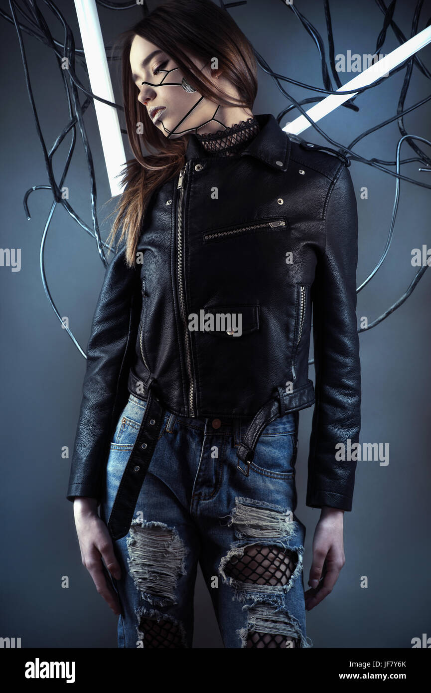 elegant robot girl in wires in style cyberpunk in leather jacket and ripped jeans - Stock Image