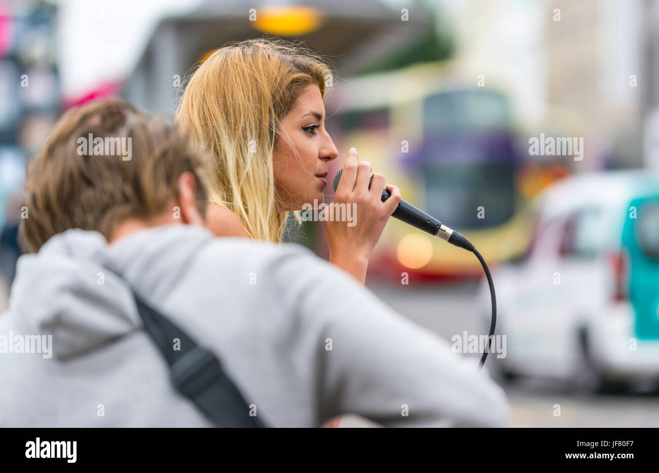 Woman singing on the street with a guitarist. Busking. Street musician. Street musicians. Female busker. - Stock Image