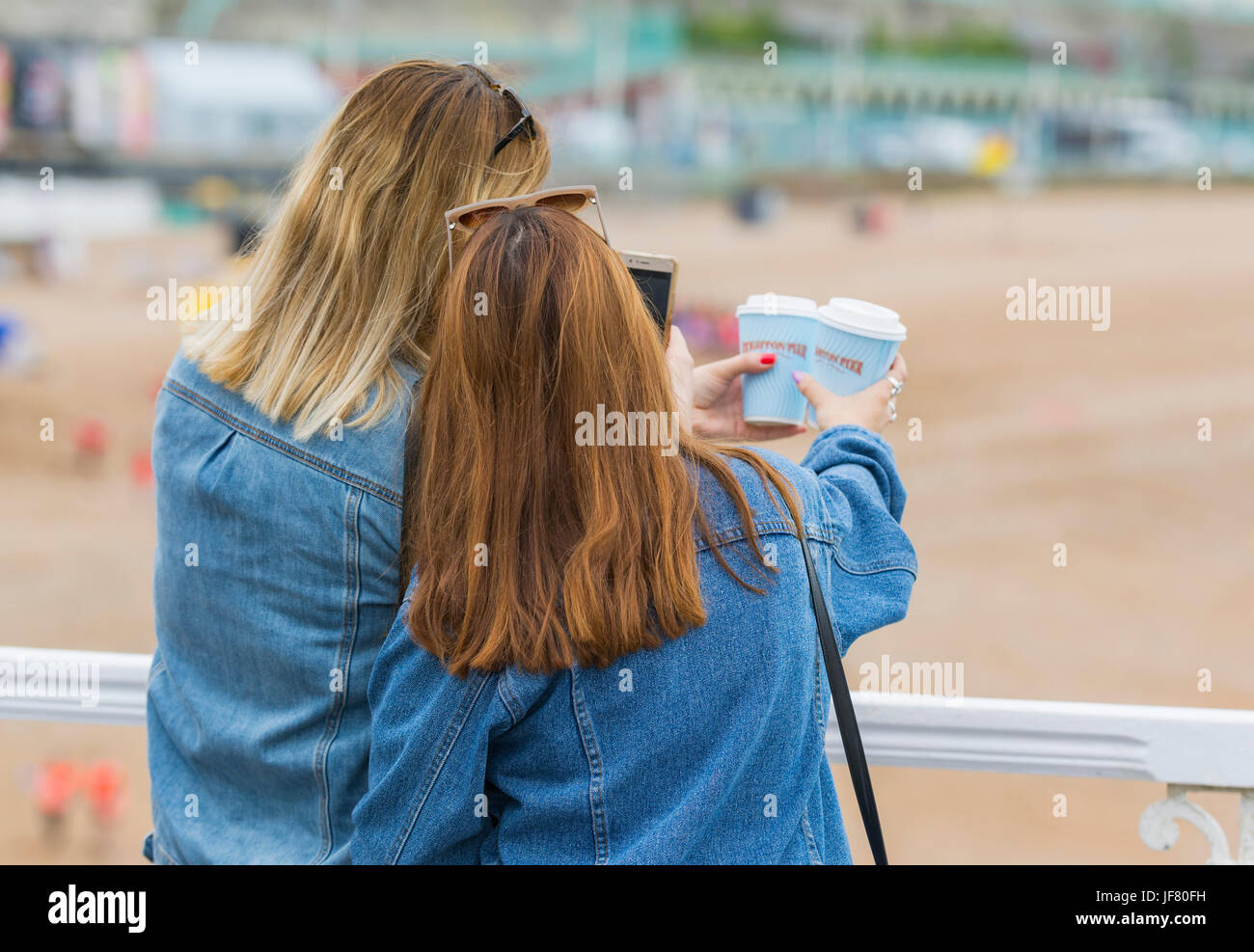 Female friends on a pier at the seaside taking photos. - Stock Image