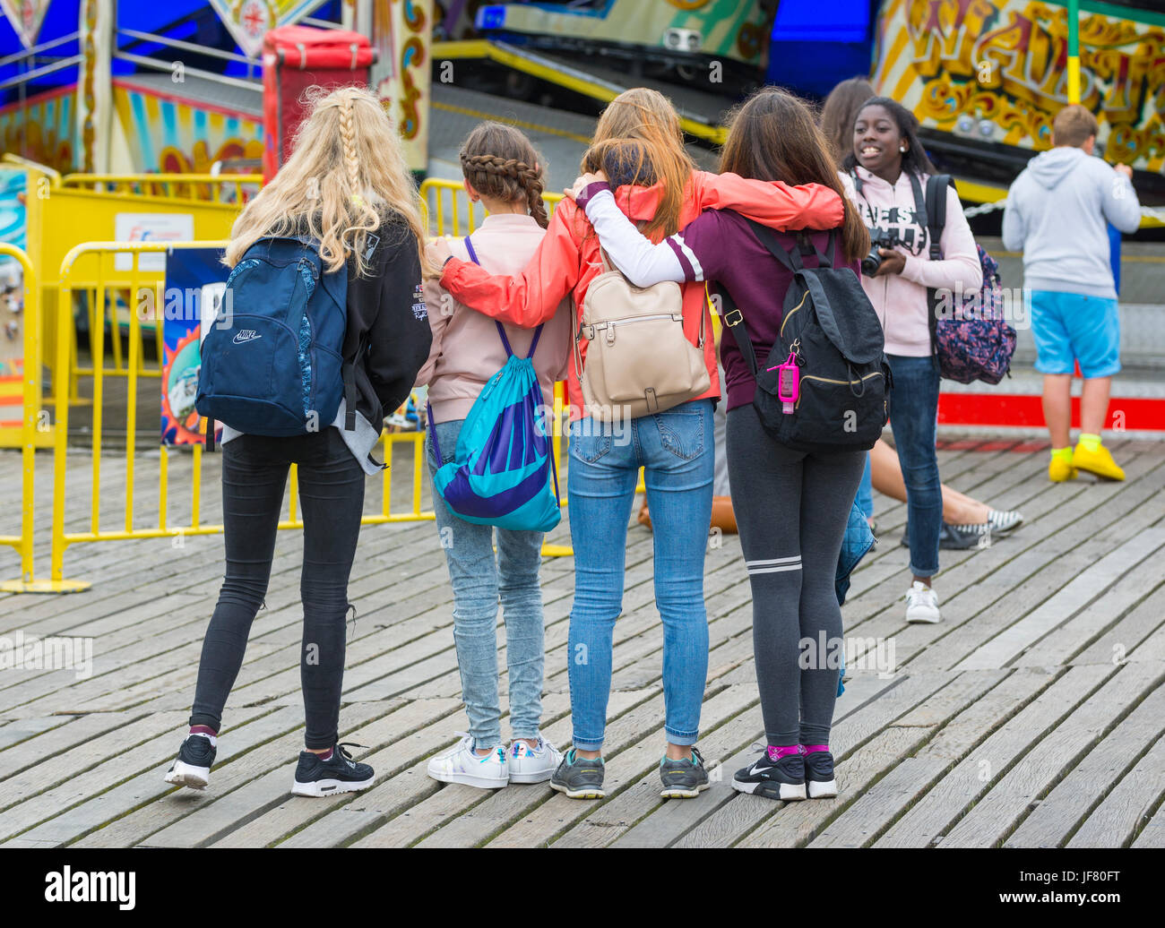 Girl taking a photo of a group of friends of a day out. - Stock Image