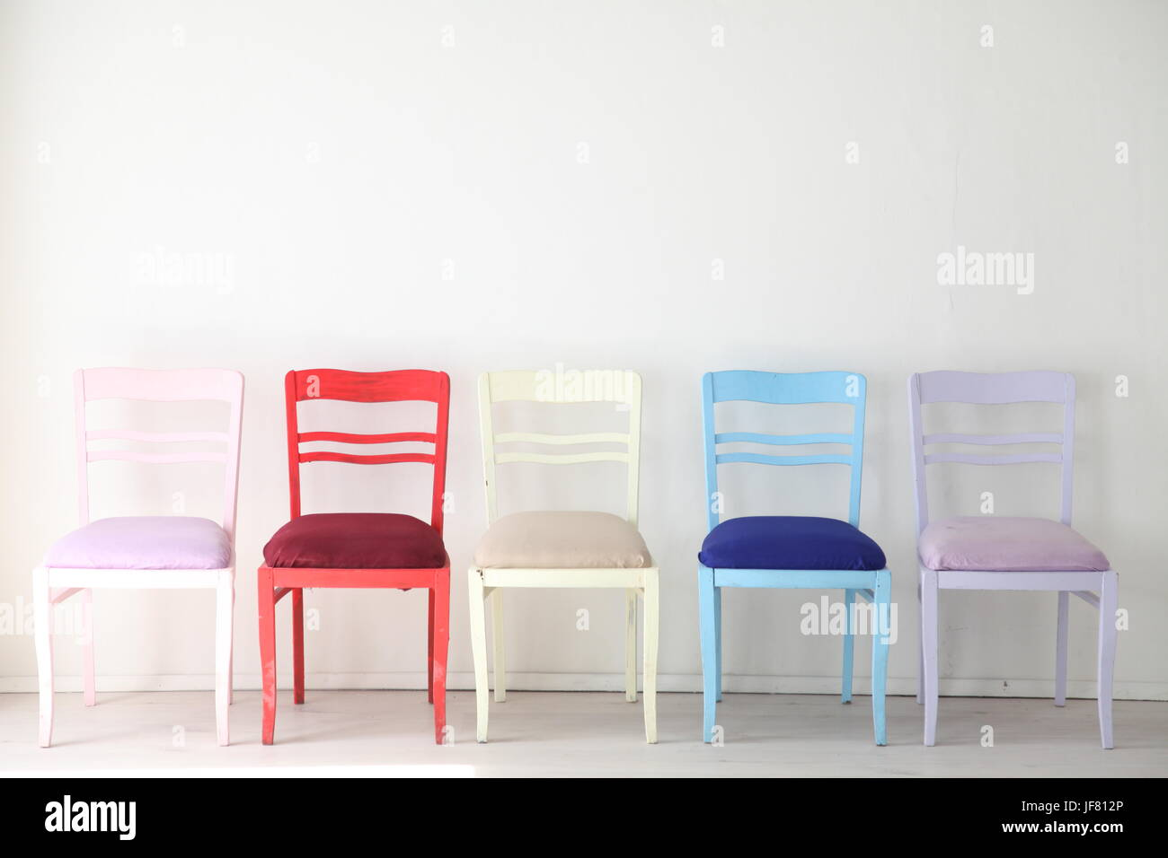 White room with colorful chairs blue yellow red blue purple - Stock Image