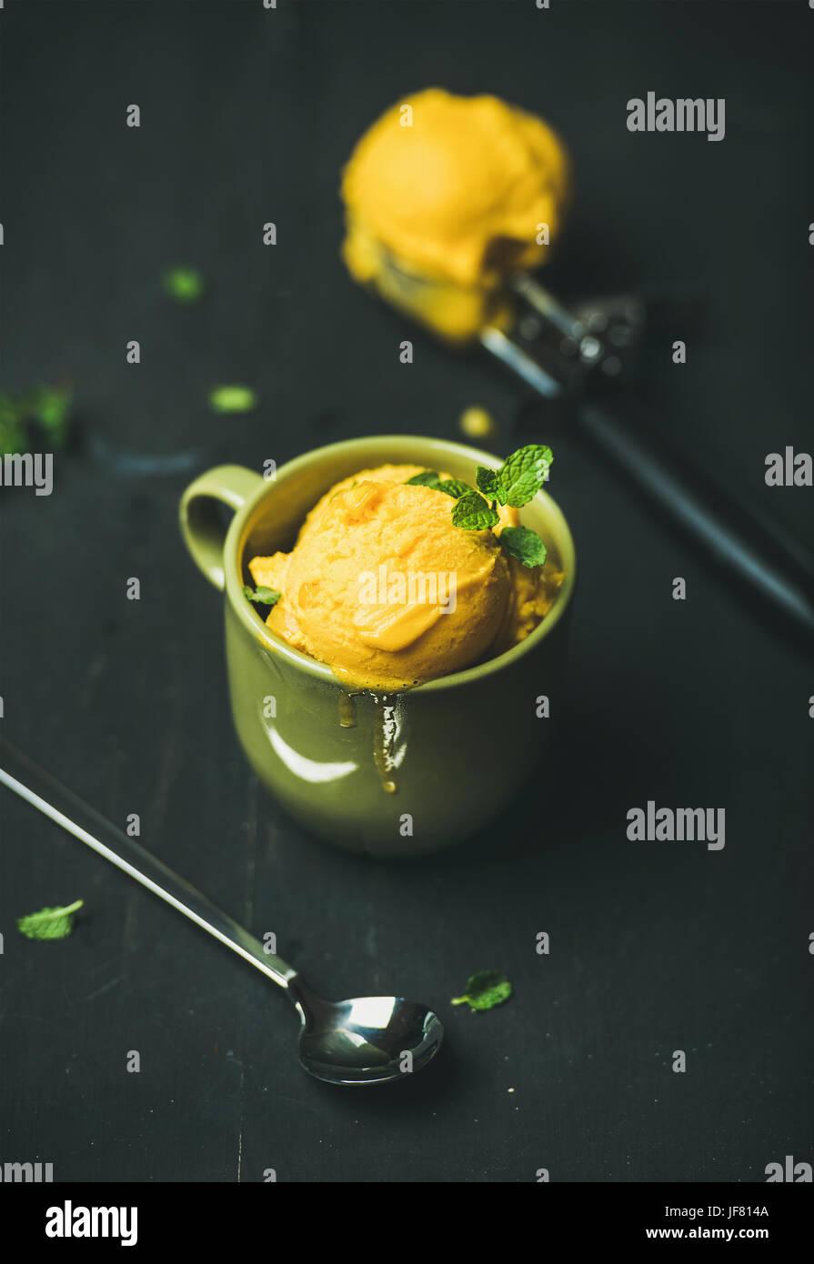 Mango sorbet ice cream scoops with fresh mint - Stock Image