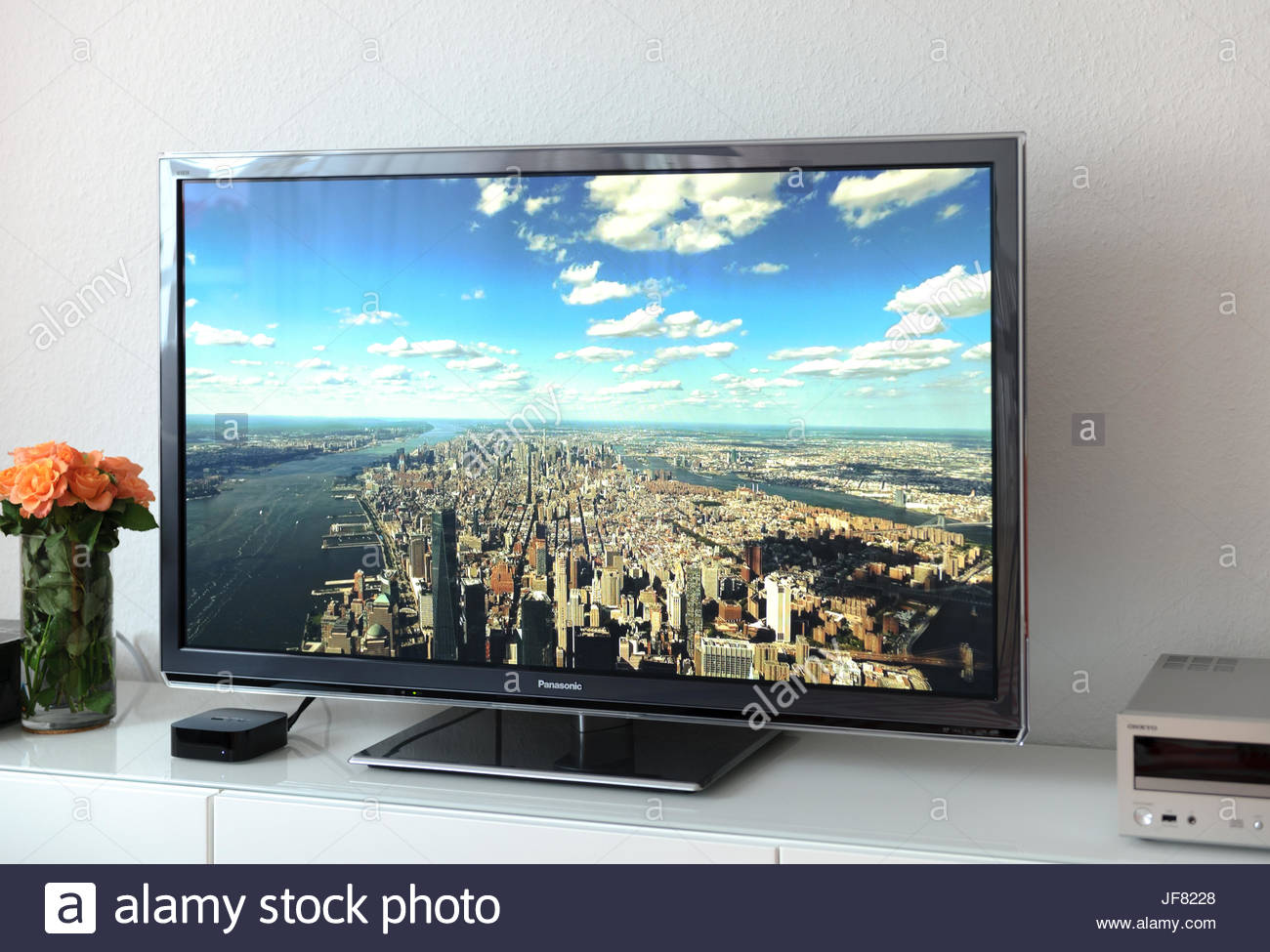 Apple TV device next to 4k Plasma Panasonic - Stock Image