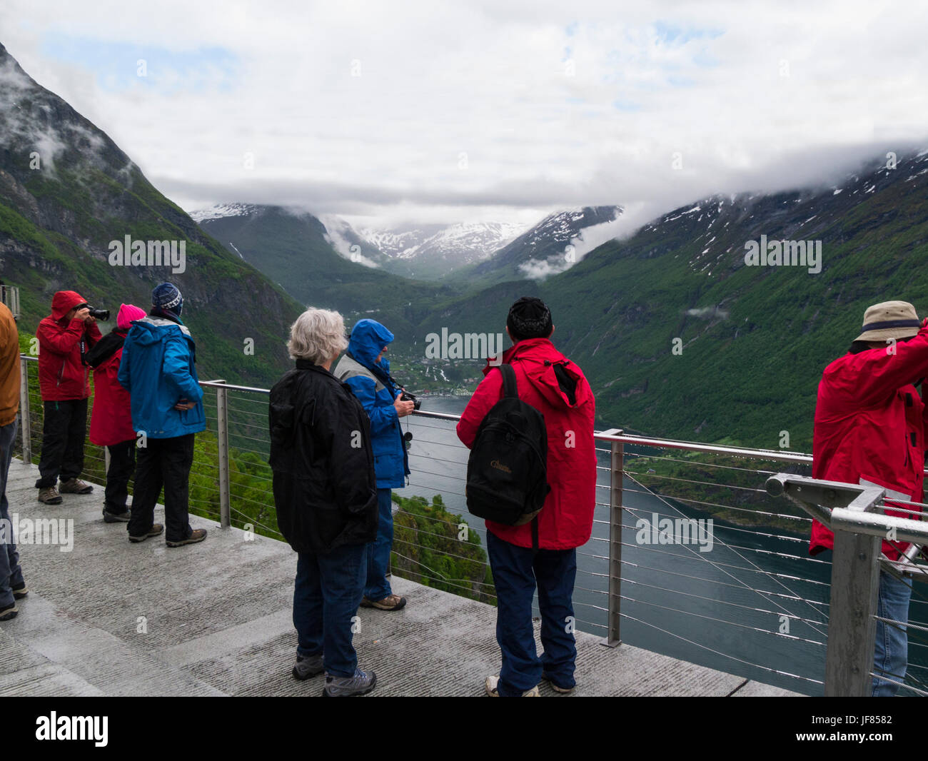 Tourists at Eagle Road Viewpoint looking down on Geirangerfjord on a cloudy day  Sunnmøre region of Møre - Stock Image