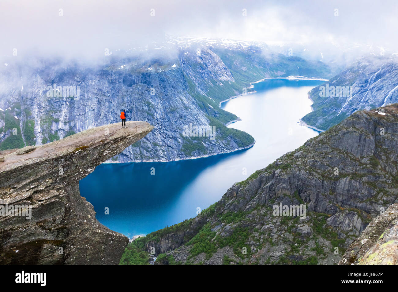Female hiker standing on Trolltunga (troll tongue) famous rock high above a lake with panoramic view of the valley, - Stock Image