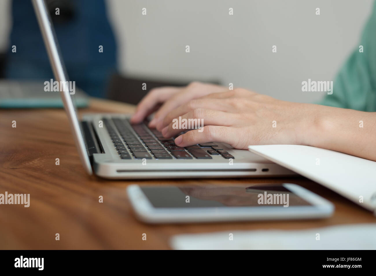 Asian male hand typing on laptop computer keyboard while working in coffee shop on workday. Freelancer lifestyle - Stock Image