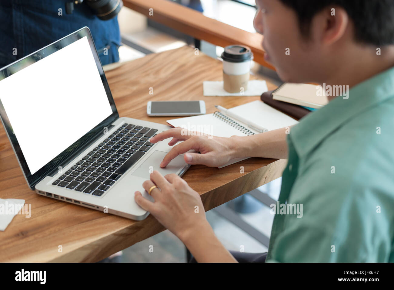 Asian hipster male with casual cloths typing on laptop computer keyboard while working  in cafe on workday. Freelancer - Stock Image