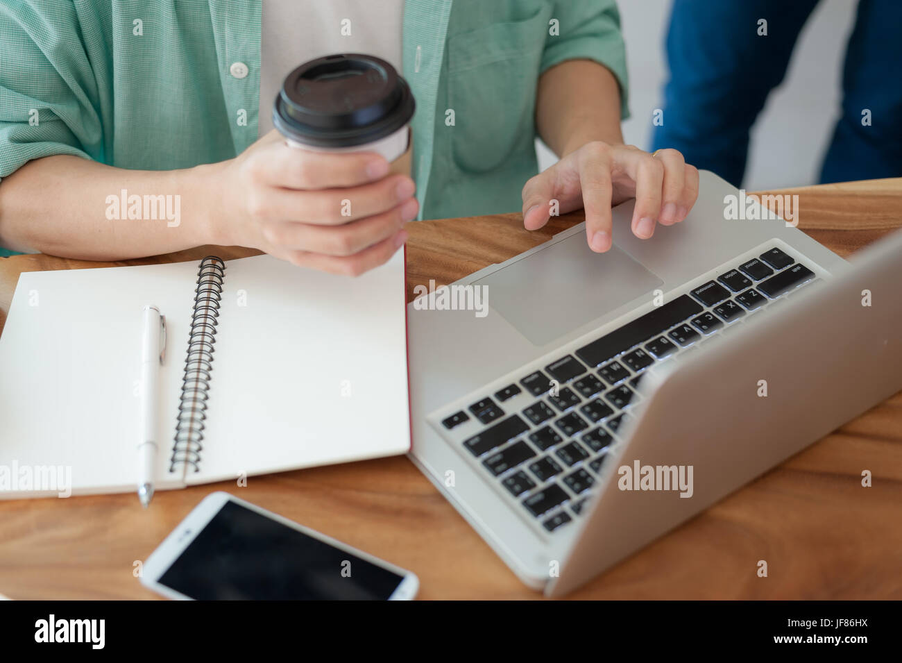 Asian hipster male with casual cloths using laptop computer touchpad while drinking coffee in cafe on workday. Freelance - Stock Image