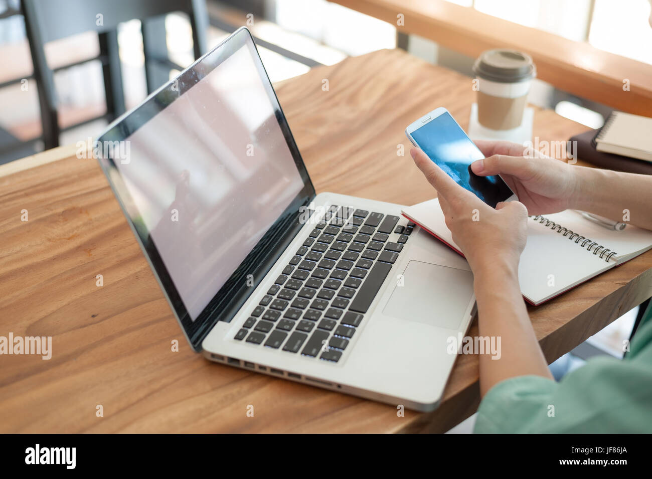 Asian hipster male using smartphone for social network while working with laptop computer in coffee shop. Freelancer - Stock Image