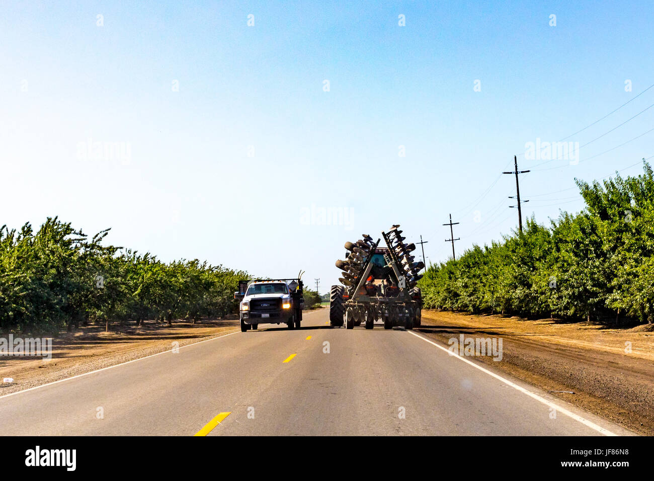 A very large tractor with disc attachment on River Road in Stanislaus County California USA - Stock Image