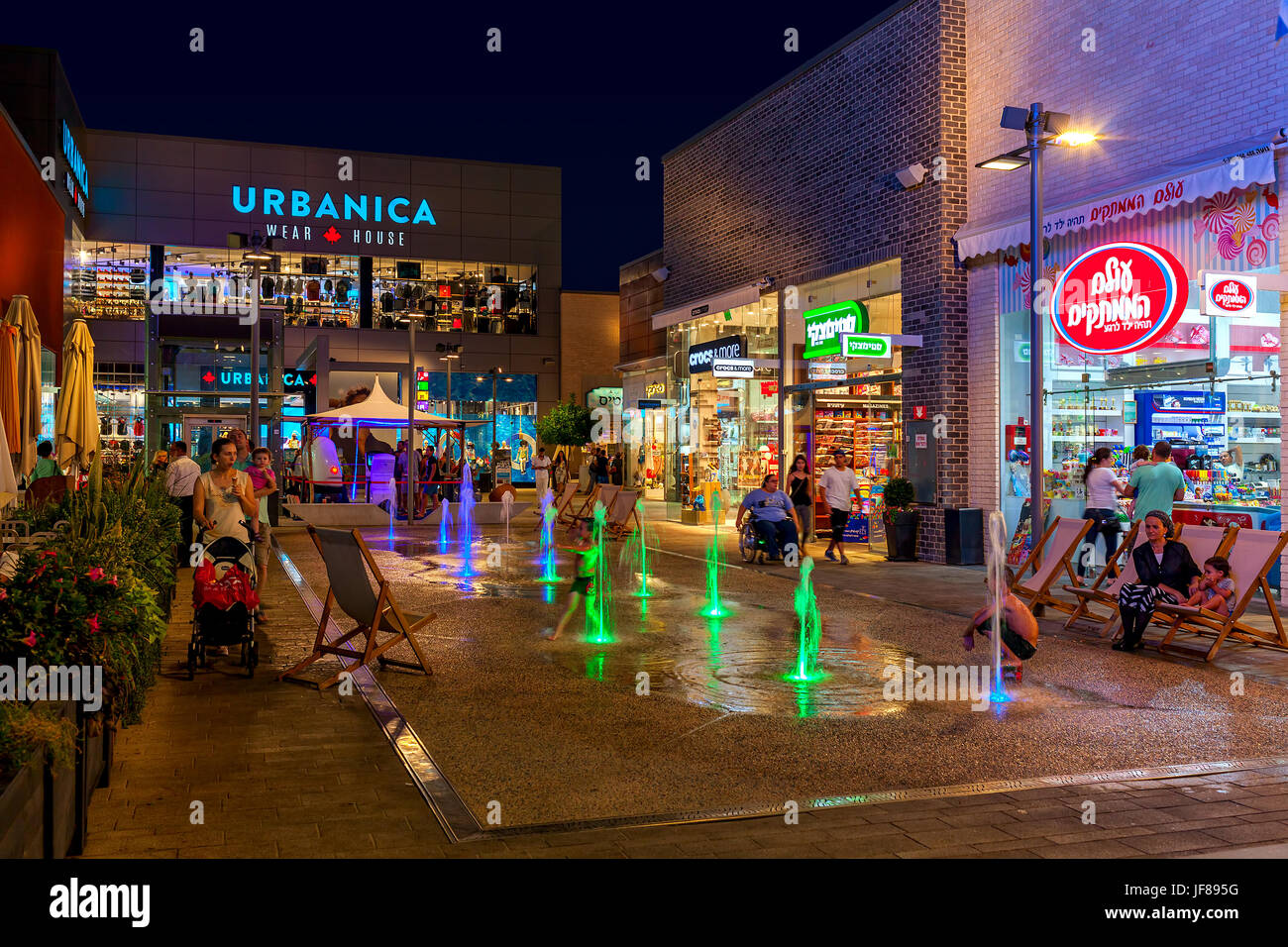 ASHDOD, ISRAEL - JULY 03, 2016: Shops, boutiques and illuminated fountains in openair mall at evening - owned by - Stock Image