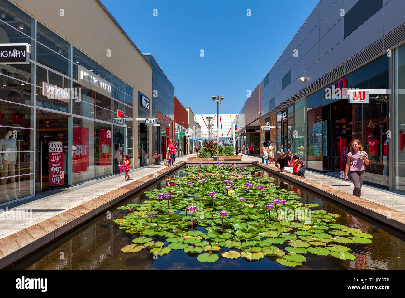 ASHDOD, ISRAEL - JULY 24, 2015: Artificial pond with flowers among shops, boutiques and contemorary stores in openair - Stock Image