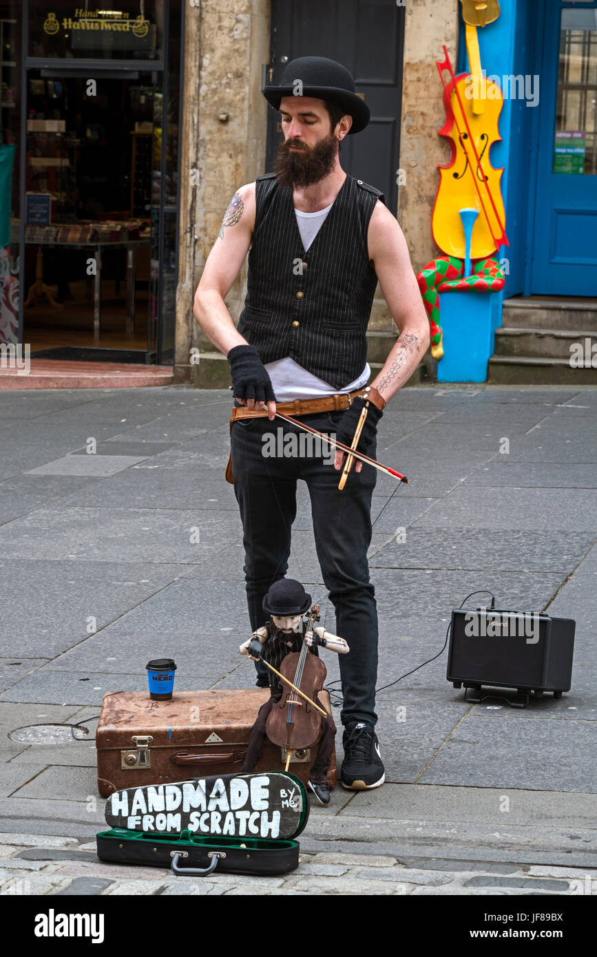 Puppeteer with a puppet of himself playing a cello on the High Street in Edinburgh, Scotland, UK. - Stock Image