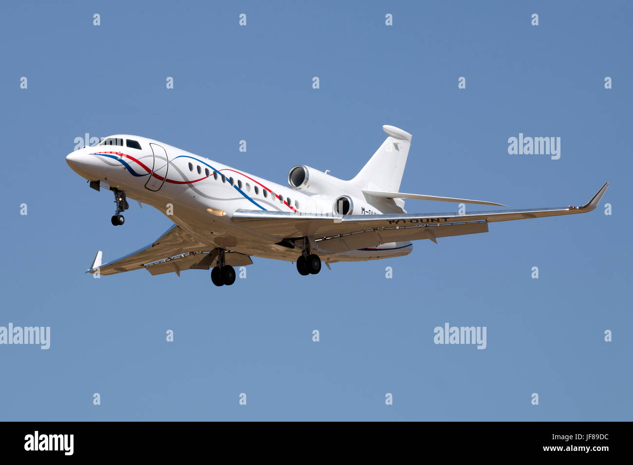 A private Dassault Falcon 7X [M-OUNT] on final approach runway 31. - Stock Image