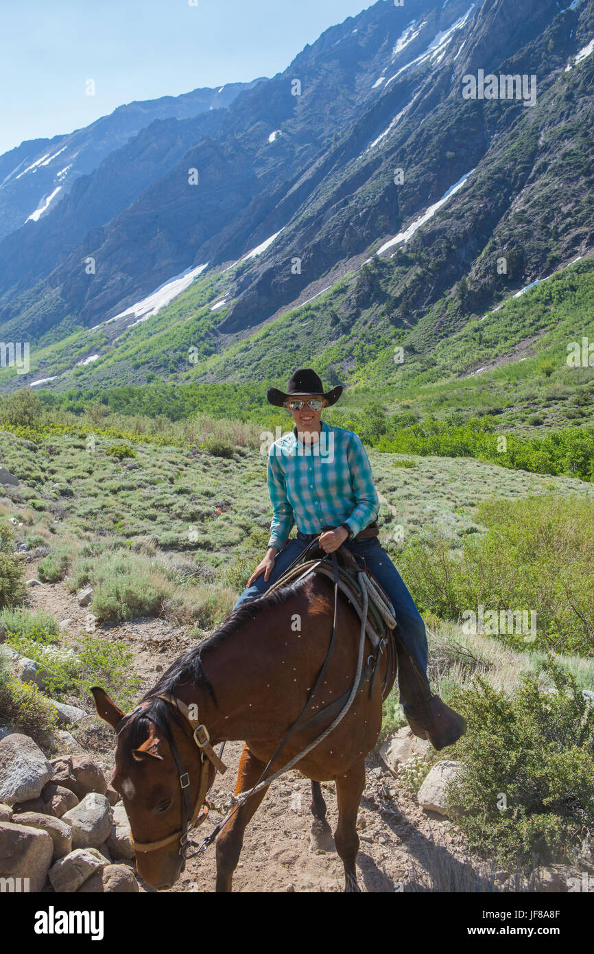 Female horseback rider  from the McGee pack station head out on the trail up McGee Canyon in the spring of 2017 - Stock Image