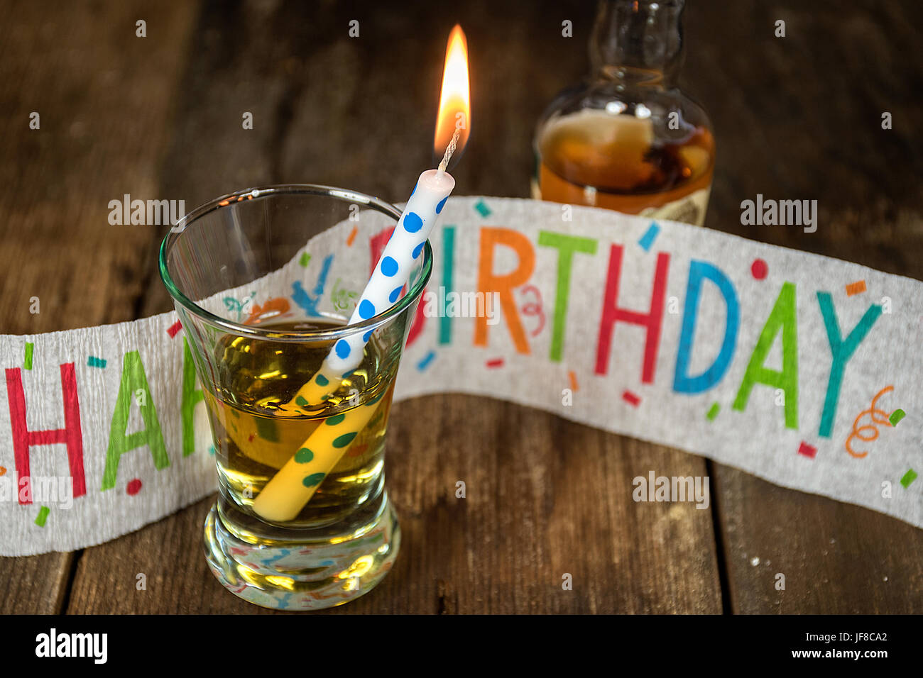 Birthday Candle With Whiskey In Shot Glass And Banner On Rustic Wood
