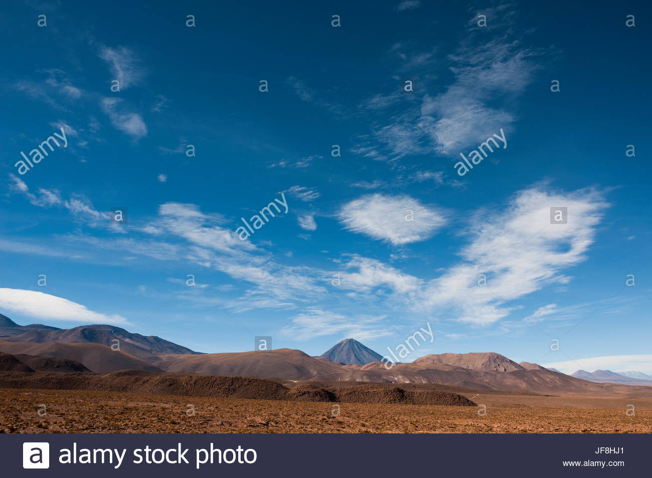 The Licancabur Volcano rises among peaks in the Andes Mountains. Stock Photo