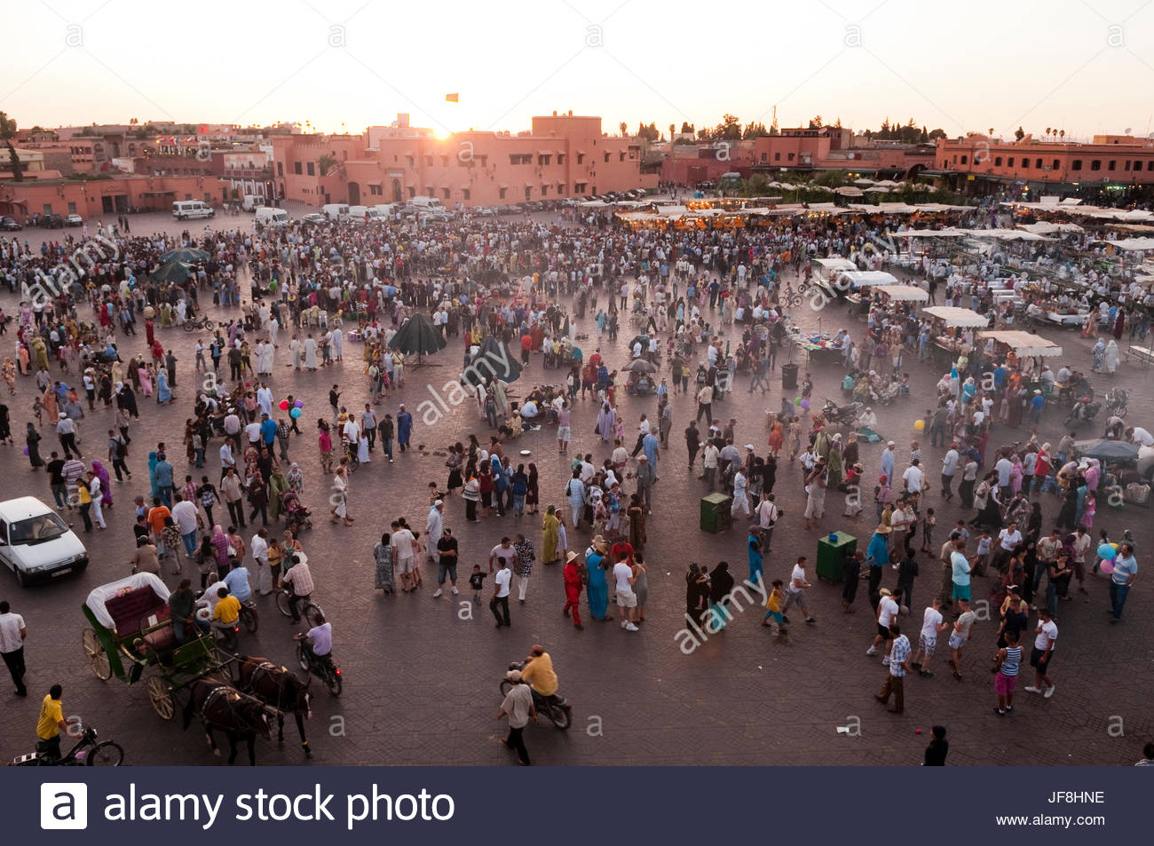 Crowds gathering in Jema al Fna Square at sunset for the nightly food stalls. - Stock Image