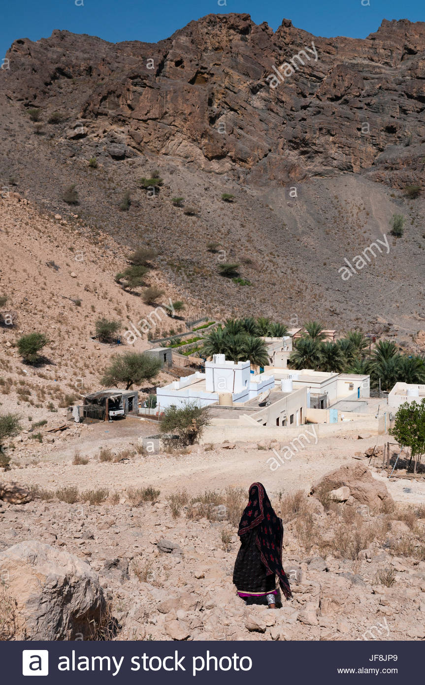 A woman walking to her house in Wadi Al Arbeieen. - Stock Image