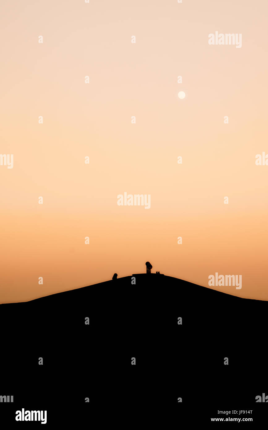Abstract creative mountain with people sitting at the top during sunset - Halde Gelsenkirchen Germany - Stock Image