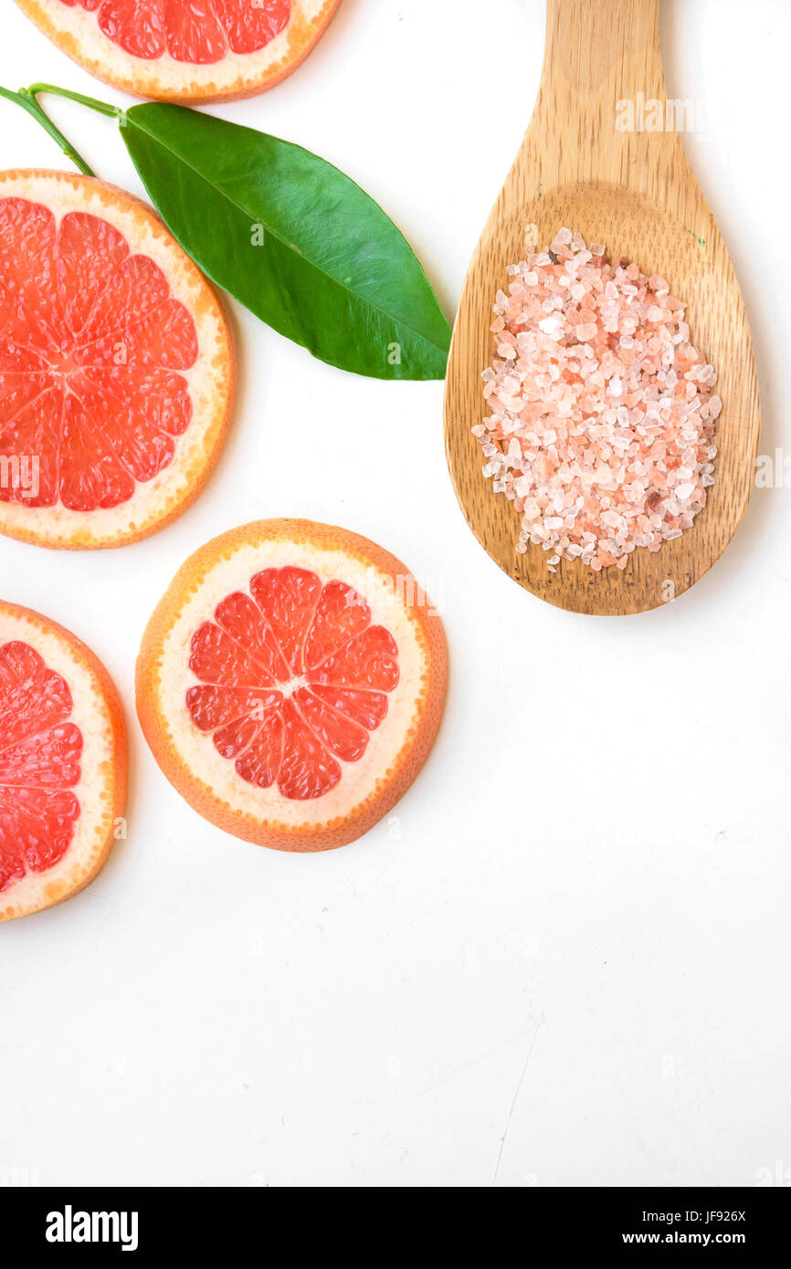 Ayurveda face skin scrub ingredients, pink Himalayan salt in wooden spoon, sliced grapefruit, green leaf on white - Stock Image