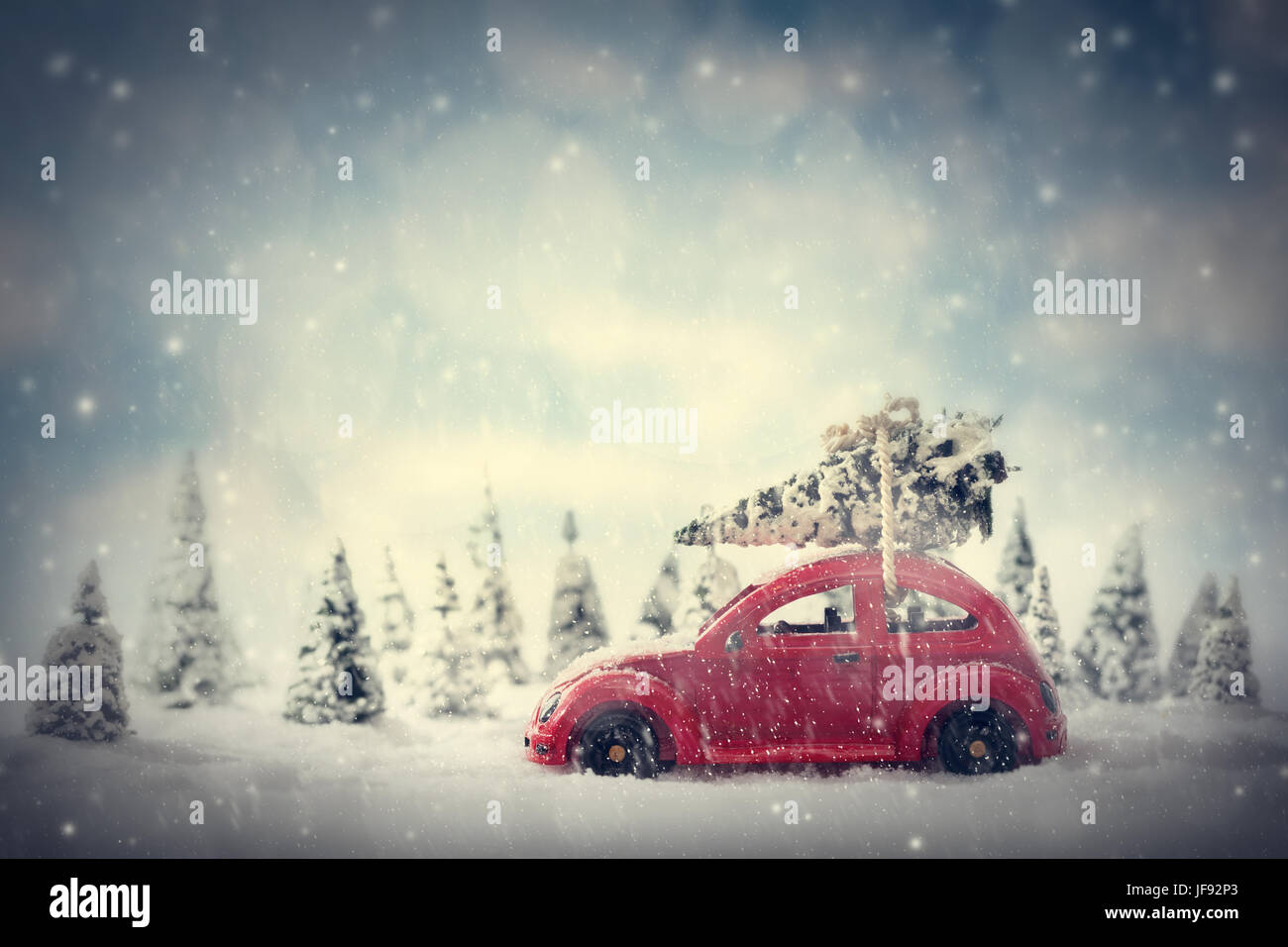 Retro toy car carrying tiny Christmas tree. Fairytale, miniature scenery with snow and forest. Stock Photo