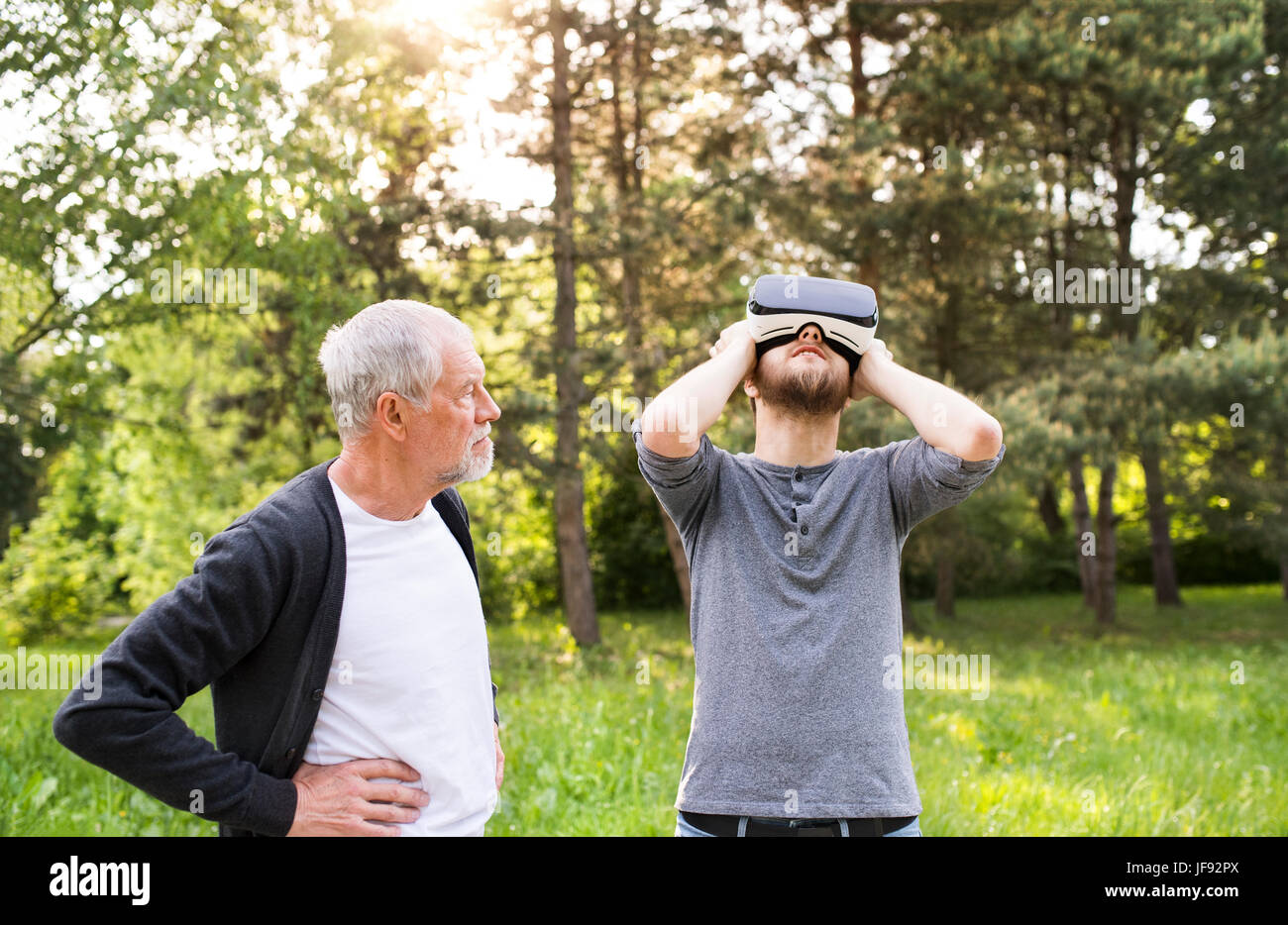 Young man and his senior father with VR glasses outdoors. - Stock Image