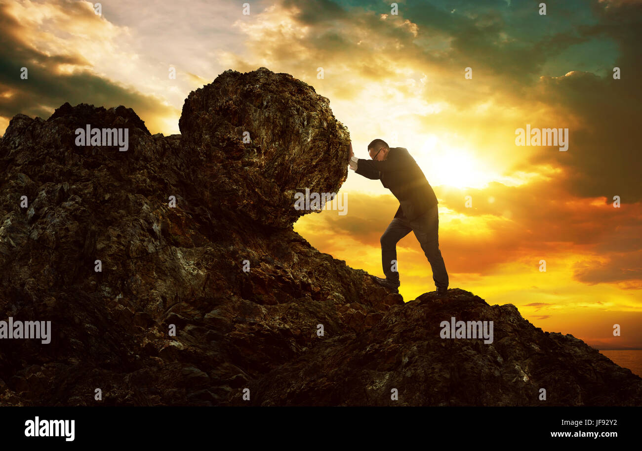 Business man pushing large stone up to hill , Business heavy tasks and problems concept. - Stock Image