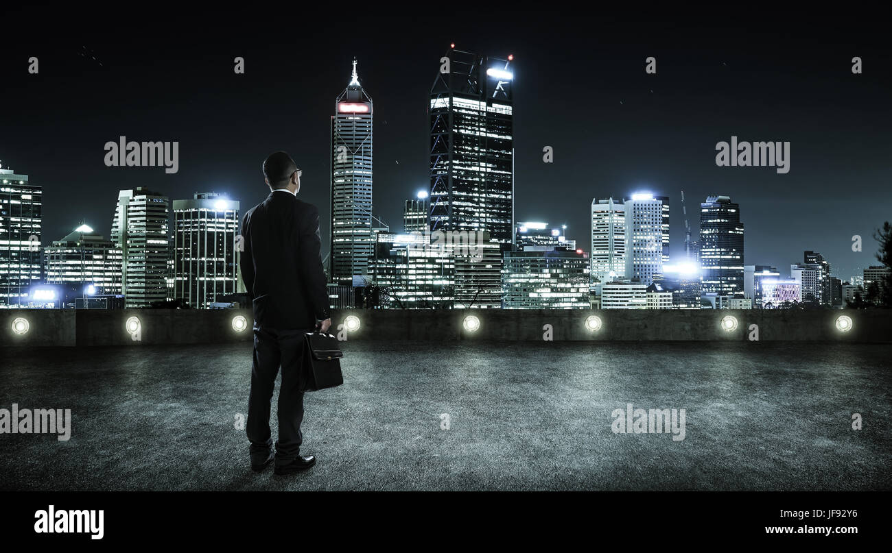 Businessman looking and thinking at roof top with modern city skyline background , night scene . - Stock Image