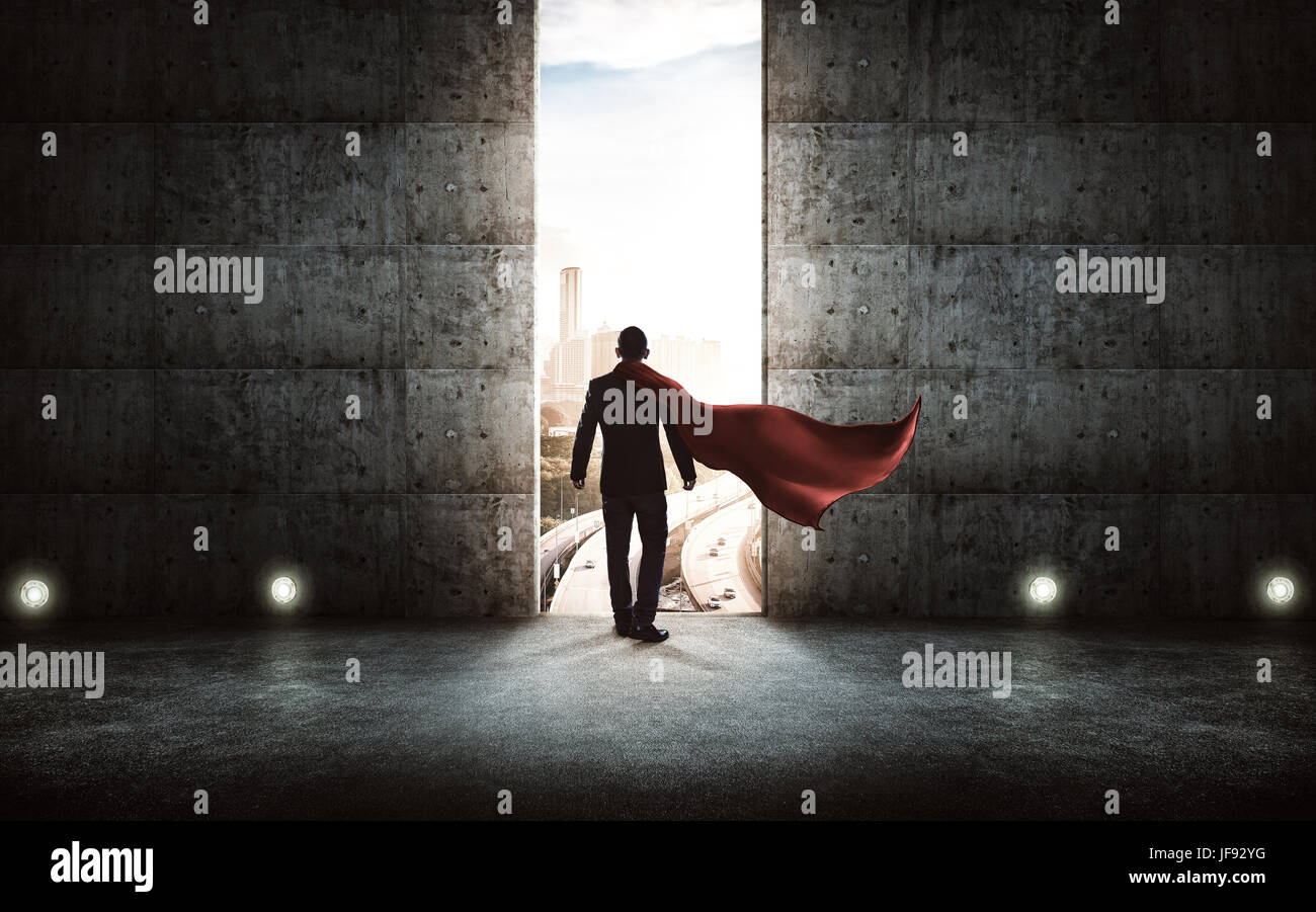 Businessman in a suit and cape stand on stair against concrete wall with huge door ,sunrise scene city skyline outdoor - Stock Image