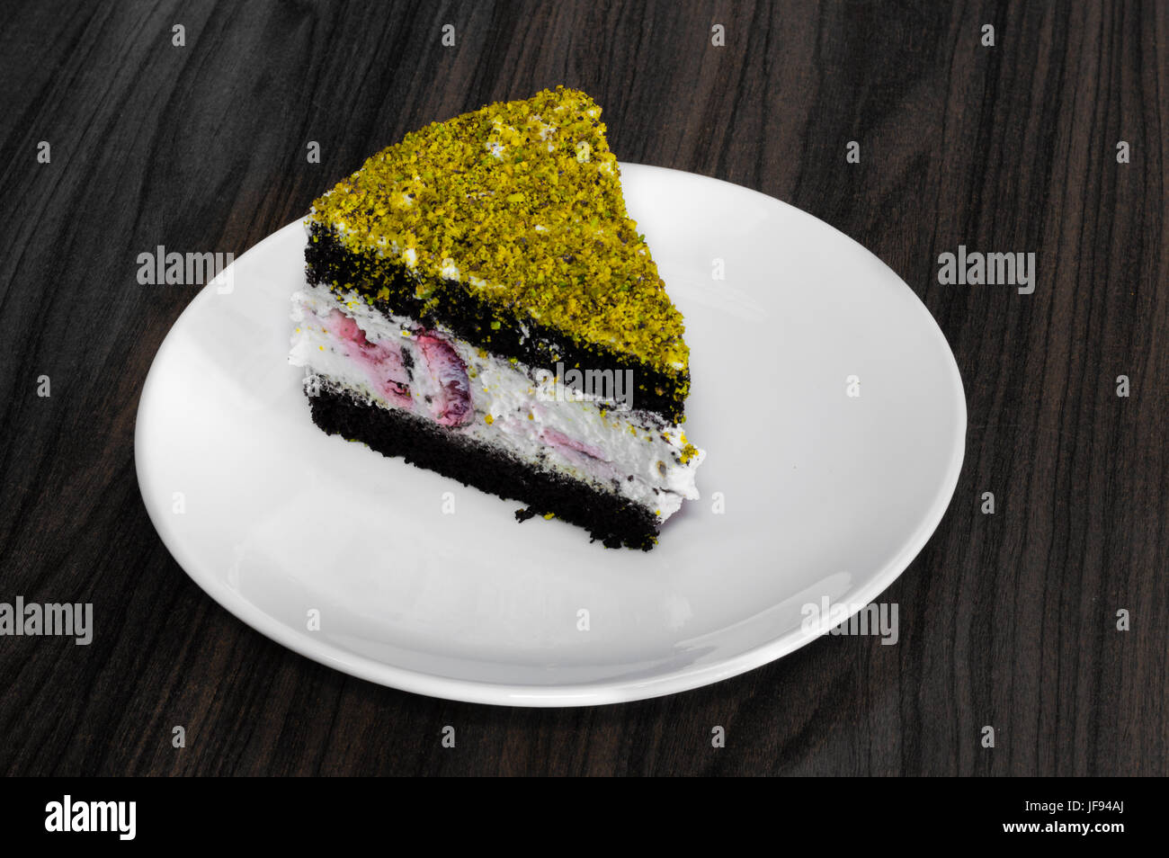 Berry and chocolate cake topped with pistachio served in a white plate on a wooden table - Stock Image