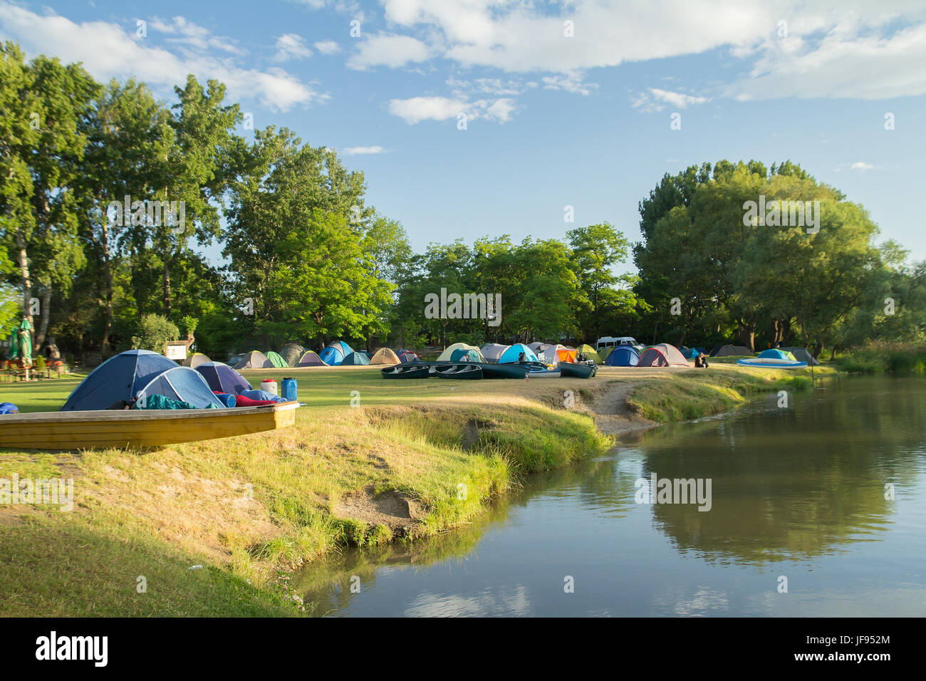 camping area with tents near river - Stock Image