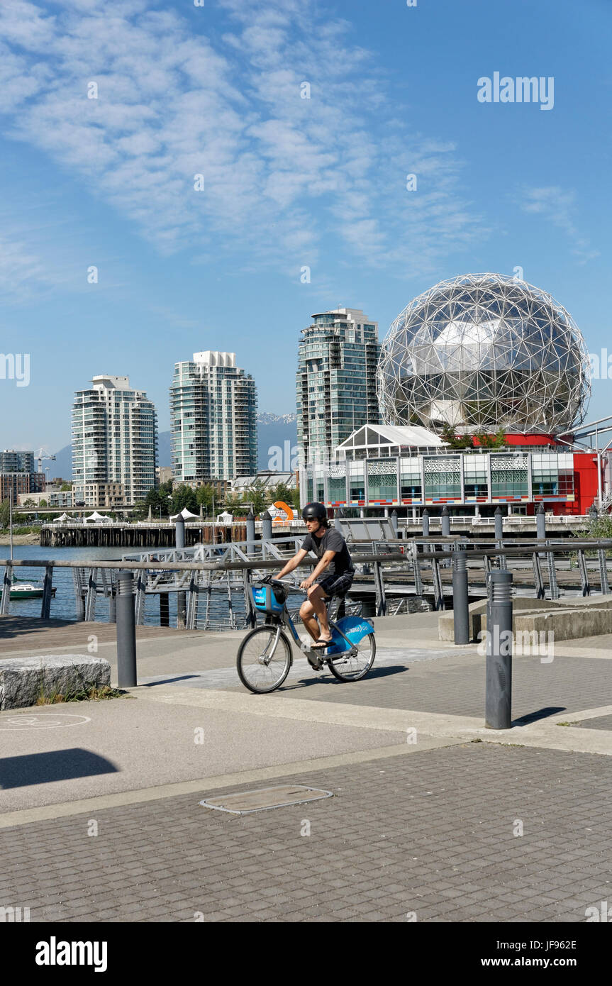 Man riding Mobi bike sharing bicycle with TELUS World of Science dome in back at the Village on False Creek, Vancouver, - Stock Image