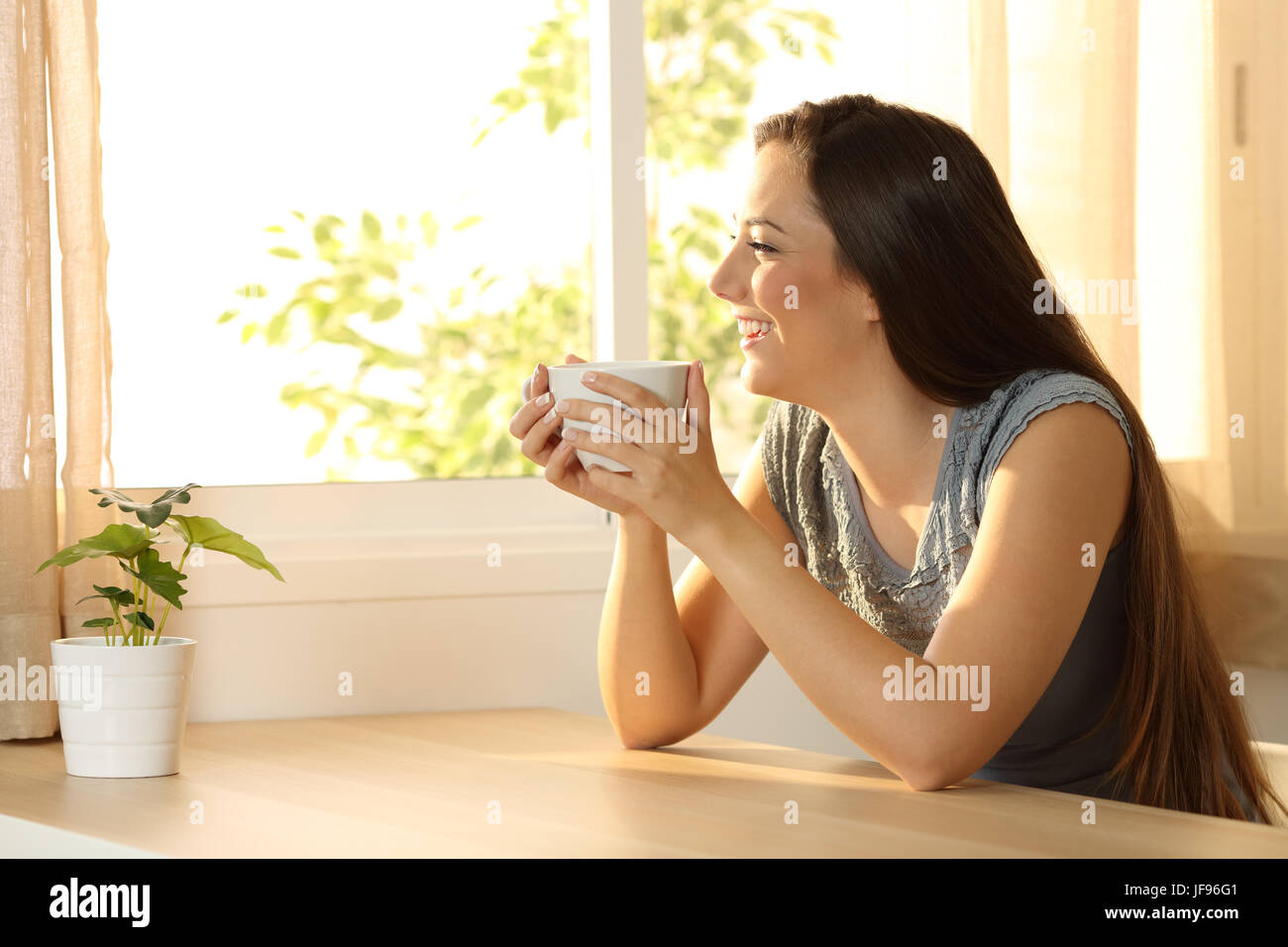 Happy woman relaxing with a coffee cup and looking through a window sitting in a table at home - Stock Image