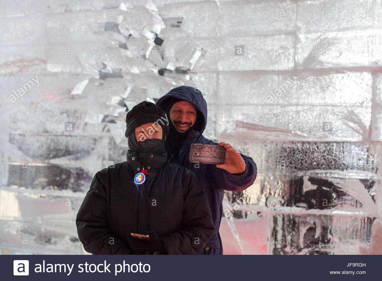 A married couple take a photo of themselves at a model of the ice hotel in Quebec City during Winter Carnival. - Stock Image